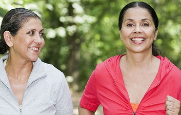 Two women outside exercising.