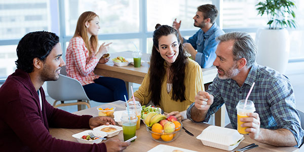 Multigenerations in workplace enjoying healthy lunch together