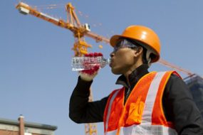 Construction worker drinking bottled water