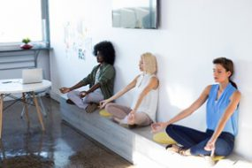 Female employees doing yoga at work