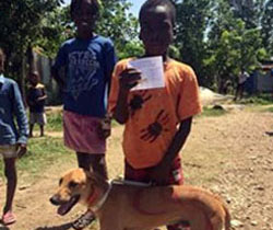 Haitian boy holds out the certificate of rabies vaccination for his dog.