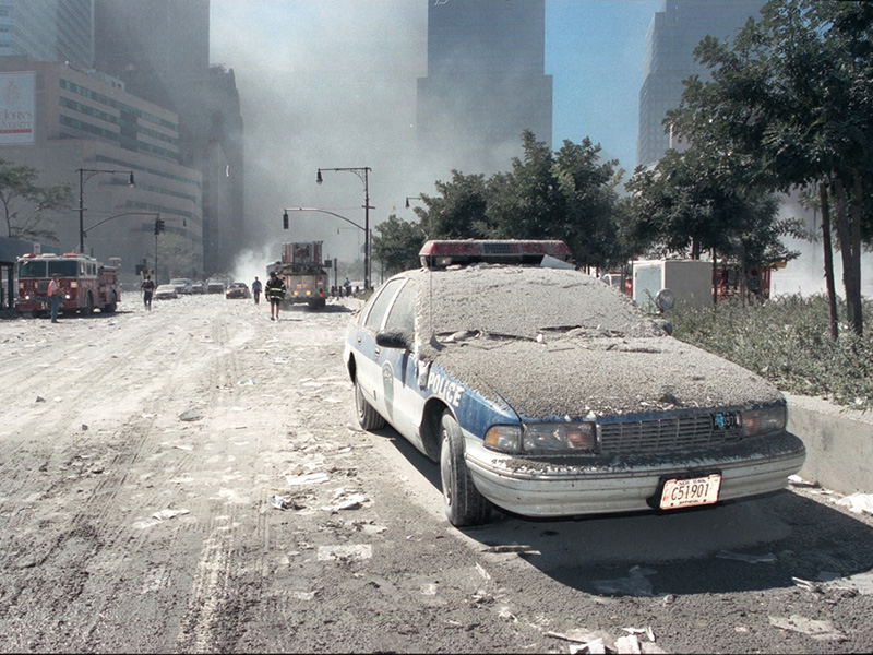 Photo of police vehicle on street, covered in a thick layer of dust from the fallen WTC buildings