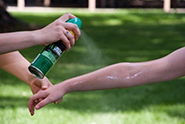 Person applying insect repellant to a childs arm