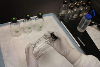 Person in lab holding a glass bottle.