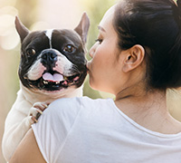 Image of a woman kissing a dog.